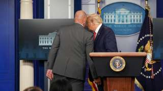 US President Donald Trump talks with a secret service agent before leaving a coronavirus briefing at the White House, August 10, 2020