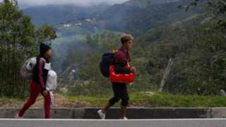 Ángel García and his partner Daniela Segueri walk along the road between Pamplona and Bucaramanga Colombia on October 1st. The couple from Valencia, Venezuela was heading to the city of Cali, and had been on the road already for seven days.