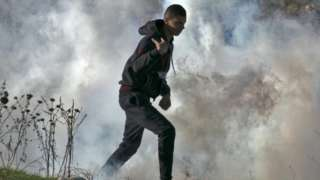 A Palestinian protestor runs for cover from tear gas fired by Israeli security forces during clashes in the West Bank