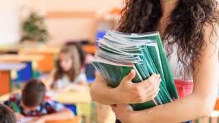 Teacher carrying books