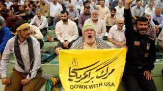 Un hombre sujeta una tela con un mensaje contra Estados Unidos en medio de un grupo de hombres en la mezquita del Imán Jomeini en Teherán, Irán, el 19 de julio de 2019