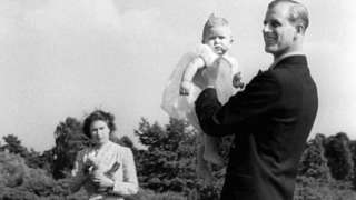 Prince Charles being lifted up by his father The Duke of Edinburgh, in the grounds of Windlesham Moor, the country home in Surrey of Princess Elizabeth and the Duke