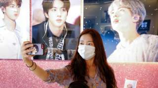 A fan of K-pop boy band BTS takes a selfie at a cafe decorated with photos and merchandise of them, in Seoul.