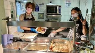 Two women behind a food serving buffet