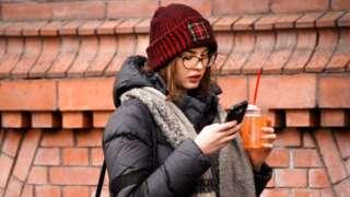 Woman scrolls through phone
