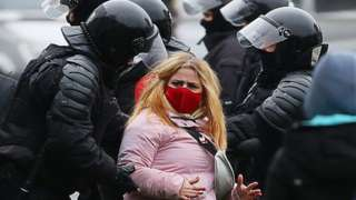Law enforcement officers detain a female protester wearing a face mask in Minsk, 15 November 2020