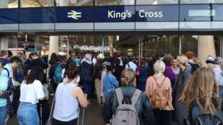 Passengers queuing after a power cut at King's Cross station