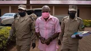 """Hotel Rwanda"" hero Paul Rusesabagina (C) in the pink inmate's uniform arriving at Nyarugenge Court of Justice in Kigali, Rwanda, on October 2, 2020, surrounded by guards of Rwanda Correctional Service (RCS)."