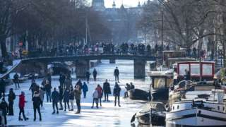 People walk and skate on ice on the Prinsengracht canal in Amsterdam, The Netherlands, 13 February 2021.