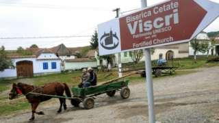 Men ride a carriage in Viscri in 2010