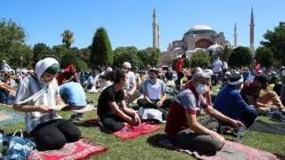 Waumini wakiwa wameweka miswala yao nje ya jengo la Hagia Sophia, wakisubiri sherehe za ufunguzi