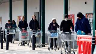 """Shoppers observe social distancing as they wait in a queue outside a supermarket in Fleet, Hampshire on March 28, 2020. - The two men leading Britain""""s fight against the coronavirus - Prime Minister Boris Johnson and his Health Secretary Matt Hancock - both announced Friday they had tested positive for COVID-19, as infection rates accelerated and daily death rate rose sharply."""