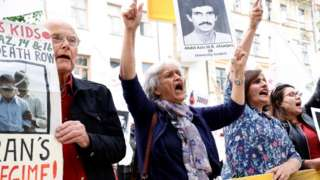 Protesters chant outside the court in Stockholm