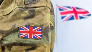Army uniform alongside UK flag