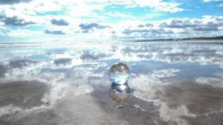 Clouds reflected in a clear ball on a beach in Alnmouth, Northumberland