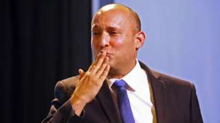 Naftali Bennett, leader of the Israeli right-wing Yamina ('New Right') party, blows kisses as he greets supporters at his party's campaign headquarters