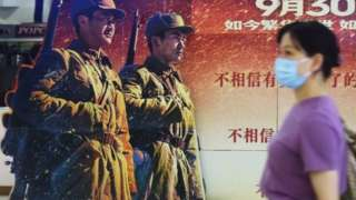A movie-goer walks by a poster for the blockbuster The Battle at Lake Changjin at a cinema in Hangzhou