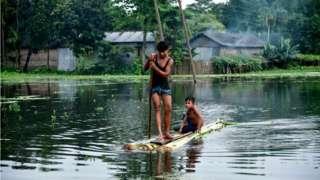 Anak-anak India menaiki rakit di Kalgachia di Barpeta, negara bagian Assam, 12 Juli 2019.