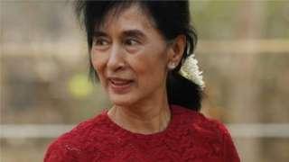 Aung San Suu Kyi carries flowers as she visits a polling station in Kawhmu township, Burma, 1 April 2012