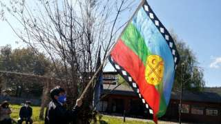 A Mapuche indigenous person holds up a Mapuche flag