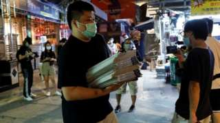 A man buys a pile of Apple Daily newspapres in Hong Kong