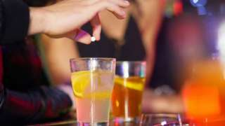 Man's hand drops pill into glass in bar