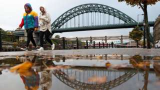 A man and women walk along Newcastle Quayside with the Tyne Bridge in the background