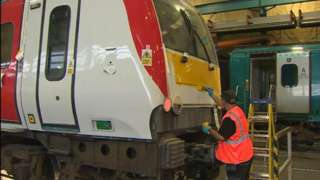A train being painted with the Transport for Wales livery