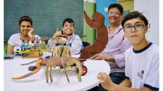 Julia, Guilherme e André exibem seus projetos de robótica na sala de recursos com o professor Edson