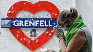 A woman stands near the Grenfell memorial wall