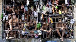 Inmates look out of an overcrowded cell in the Penal Center of Quezaltepeque, El Salvador. 9 November, 2018
