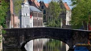 Foto de uma paisagem belga: rio, ponte e casas ao fundo