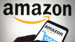 The Amazon logo is seen on a smartphone and a pc screen