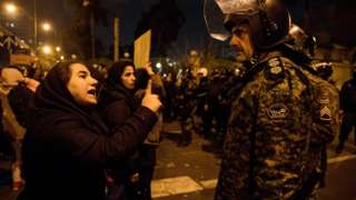A woman attending a vigil in Tehran for those killed in the Ukraine International Airlines plane crash confronts a policeman (11 January 2020)