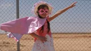 Refugee girl posing as super hero