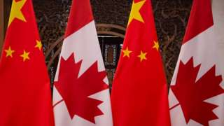 Canadian and Chinese flags are seen in Beijing