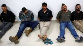 Men accused of the president's assassination sit against a wall