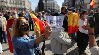 """A demonstrator holds a poster reading """"Government Resignation"""" during a protest against coronavirus restrictions in Madrid"""