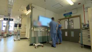 Hospital scene, with medic looking at screen