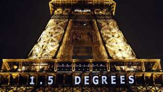 """Eiffel Tower illuminated with a sign reading """"1.5 degrees"""""""