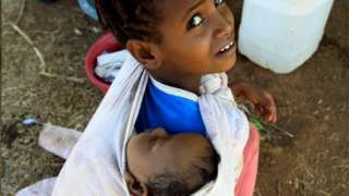 An Ethiopian refugee child from Tigray carries her sibling in the Um-Rakoba, Sudan. Photo: December 2020