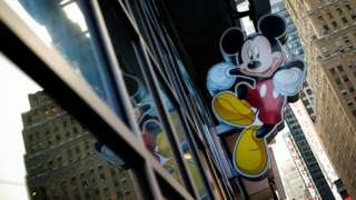 An image of Mickey Mouse, the official mascot of The Walt Disney Company, is displayed outside the Disney Store in New York
