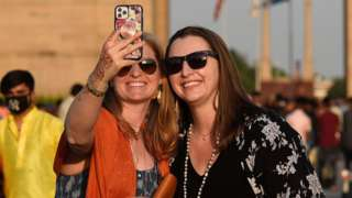 Foreign tourists are seen at India Gate monument