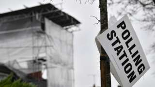 Polling station sign falling off a lamp-post