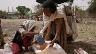 An aid worker distributes measured portions of yellow lentils to residents of Geha subcity