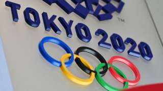 The Olympic rings and Tokyo 2020 branding are seen in relief in a wall