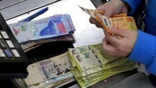 Una persona contando pesos