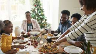 Family around dining table at Christmas