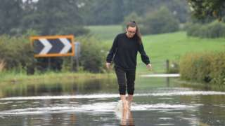 A woman makes her way along the flooded Bonis Hall Lane, Prestbury, Cheshire