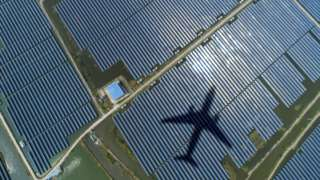 Solar energy panels with shadow of a plane